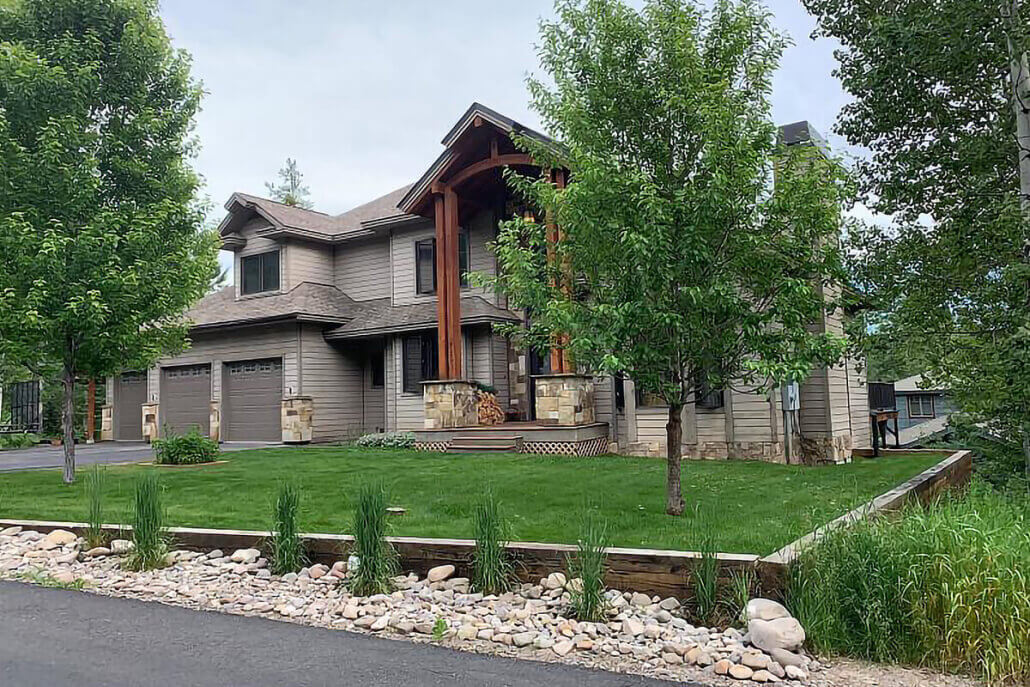 large house with tall wood beams and three car garage