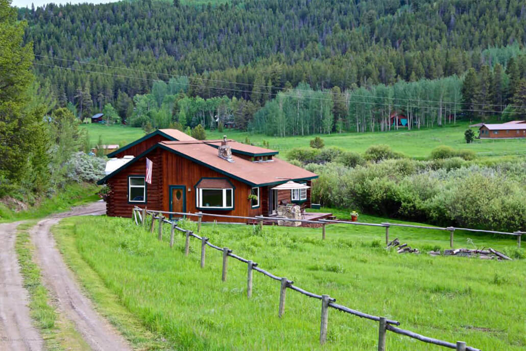 small brown log home in green valley