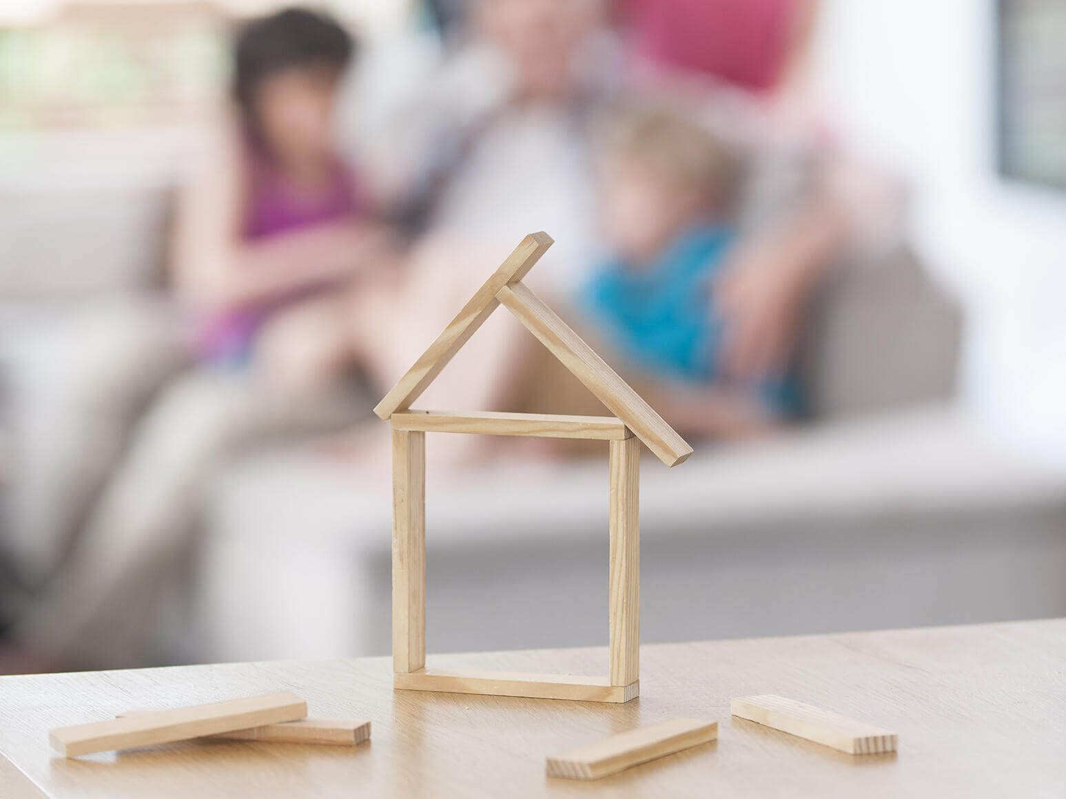 wooden sticks on table in shape of house with family blurred in background