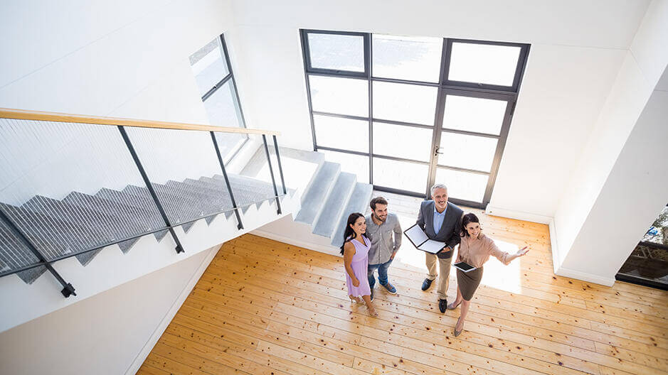 view looking down into foyer at realtors showing couple a new house