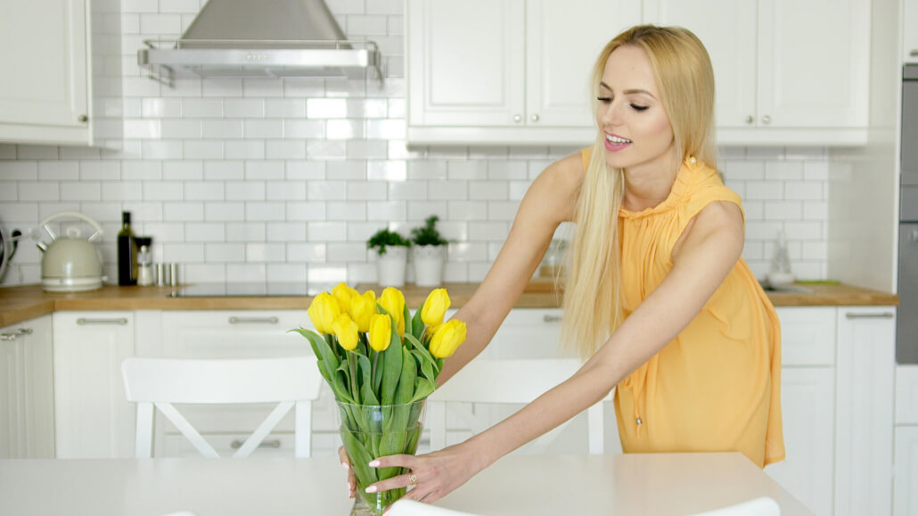 woman setting yellow tulips on counter in white kitchen
