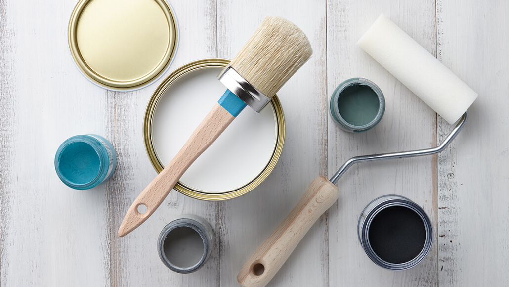 paint brush, paint roller and several small cans of different colored paint